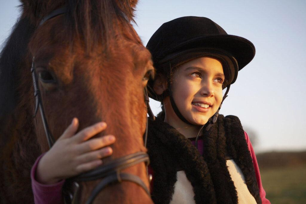 Una bambina abbraccia il suo cavallo.