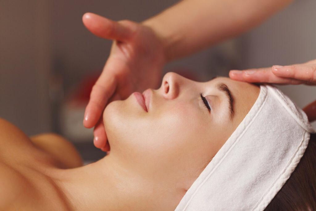 Una donna viene massaggiata sul viso