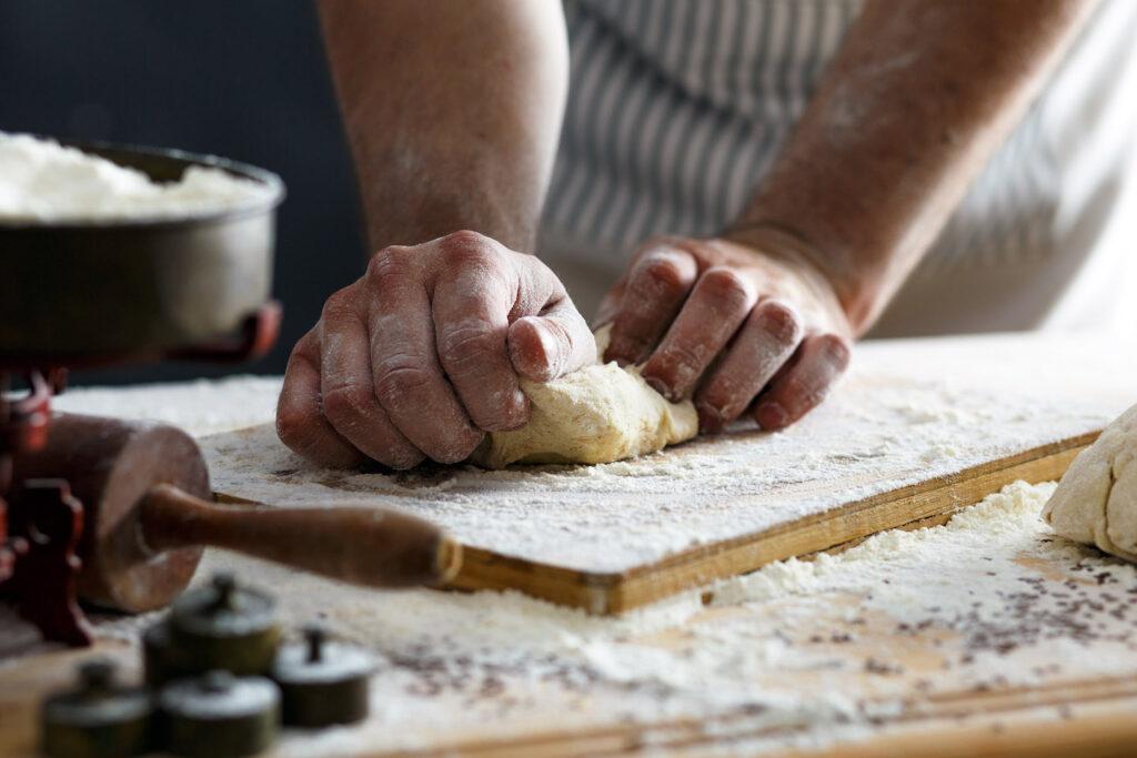 Uno chef impasta a mano la pasta fresca.