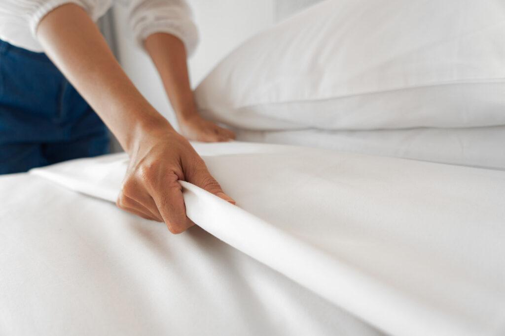 Una donna che rifà il letto
