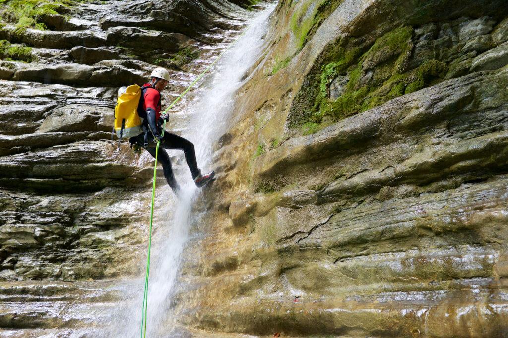 Un uomo si cala con la corda praticando il torrentismo.
