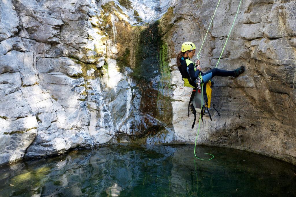 Una donna si cala con la corda praticando il torrentismo.