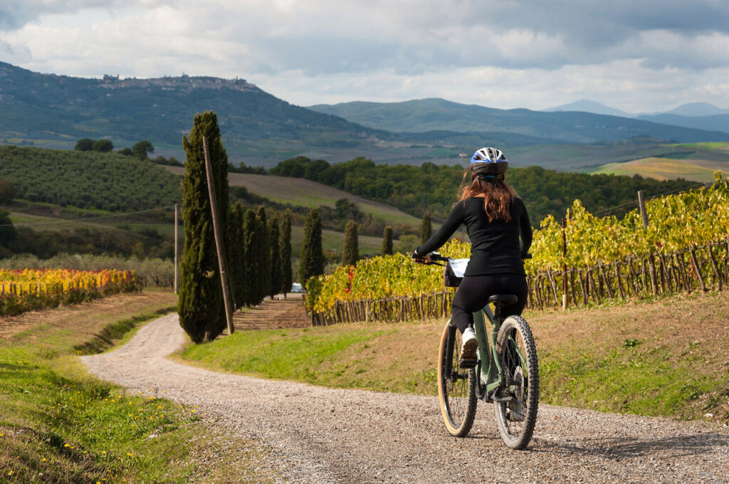 Una donna che pedala, immersa nella campagna umbra, circondata da uno splendido vigneto.
